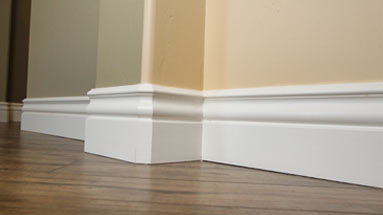 Baseboard molding installed over hard wood